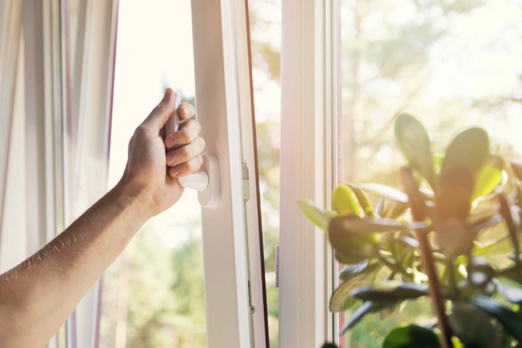 Une personne ouvre la fenêtre pour faire aérer et améliorer la qualité de l'air intérieur