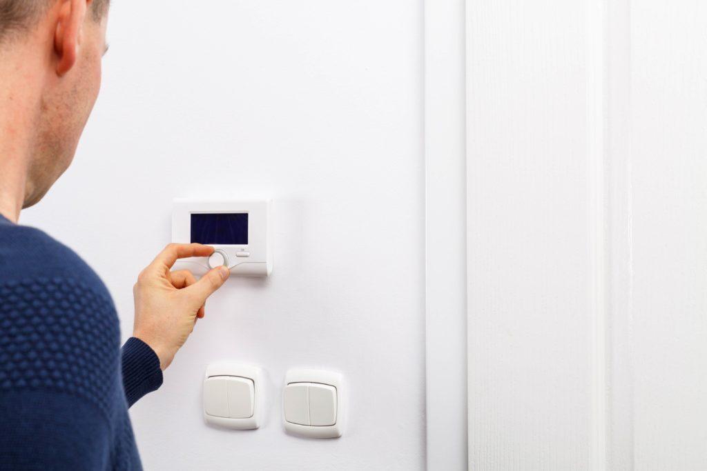 Une main actionne un bouton d'un panneau de contrôle du chauffage intérieur pour réduire la facture d'énergie