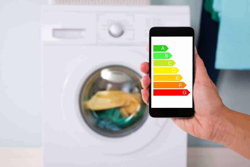 Un smartphone affiche une étiquette énergie correspondant à un lave linge en fond
