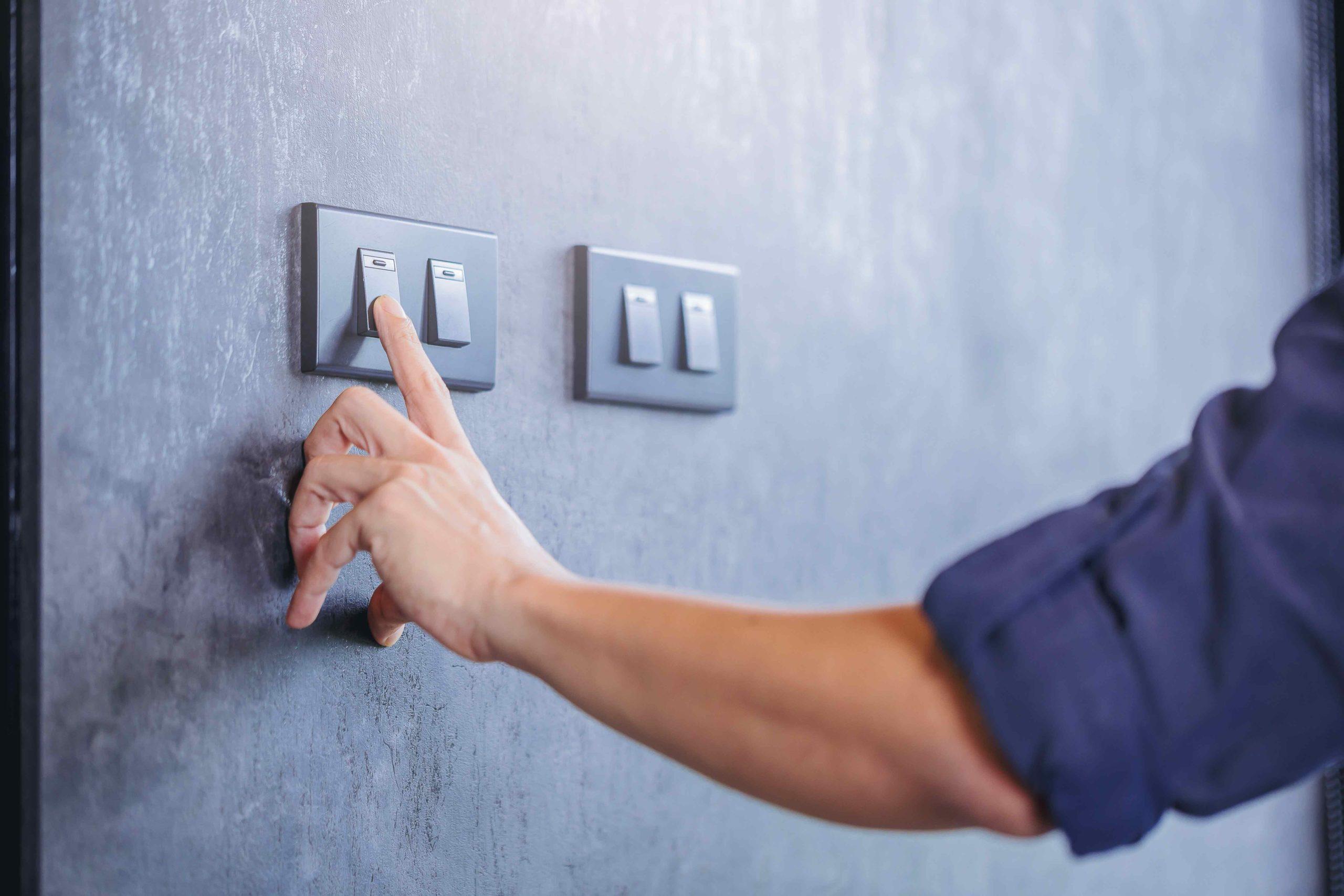 Une homme appuie sur un interupteur afin d'éteindre la lumière pour faire des économies d'énergie